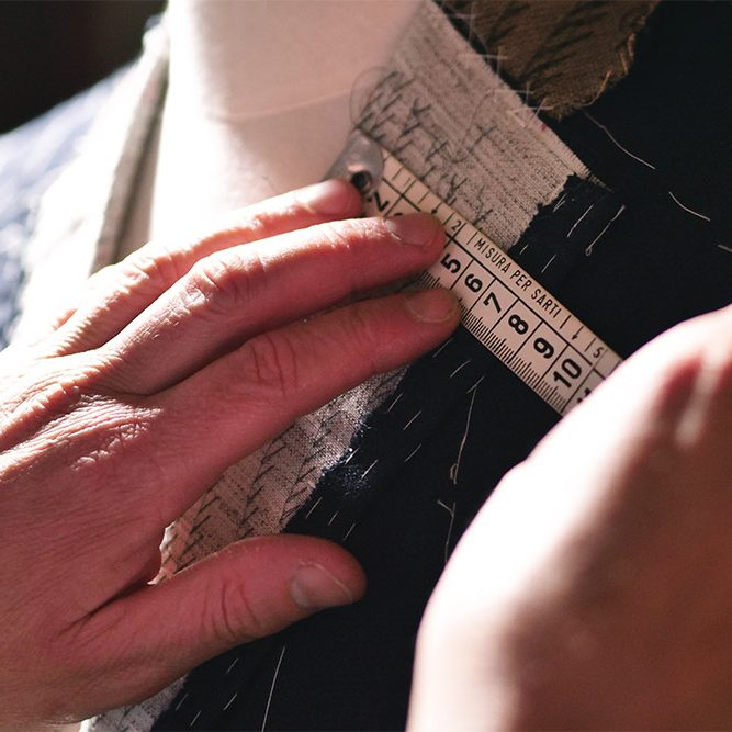 Portarit of a tailor while making a business suit using the tape